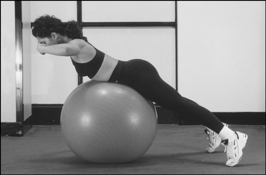 Perform the back extension on a physioball to add variety to your workout. [Credit: Photograph by S