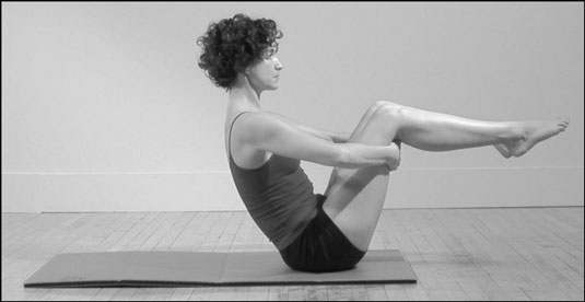 Woman does the Balance Point position in Pilates.