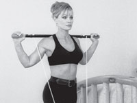 Woman holds an exercise bar across her shoulders.