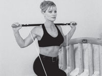 Woman does a lunge while holding an exercise bar.