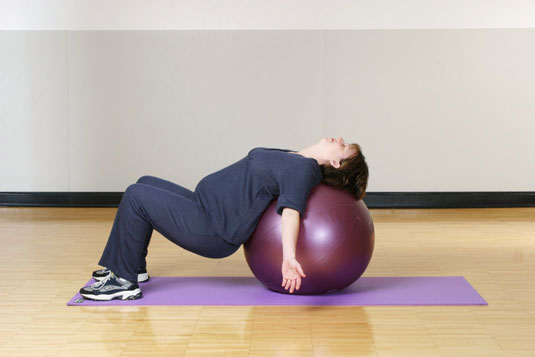 An oversized plastic ball is a nifty flexibility gadget, perfect for exercising during pregnancy. [