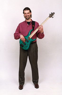 The position of your bass shouldn't change much whether you're sitting or standing.