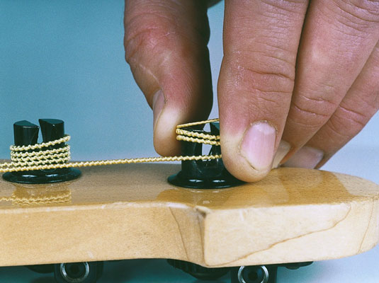 Cut the string and pull the coiled part from the tuning post.