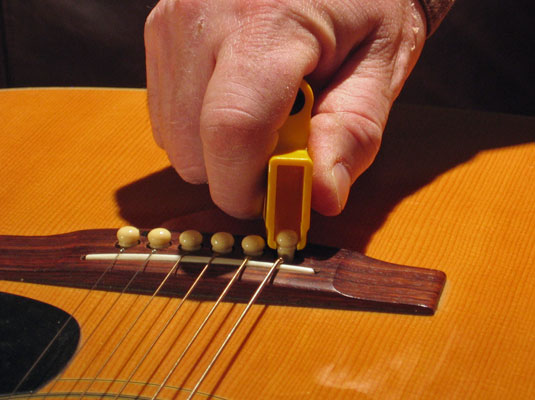 Popping out the bridge pin of an acoustic guitar.