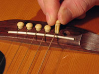 Wedging the bridge pin back into the acoustic guitar.