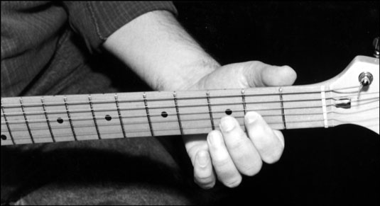 The electric guitar neck lies comfortably between the thumb and the first finger as the first finge