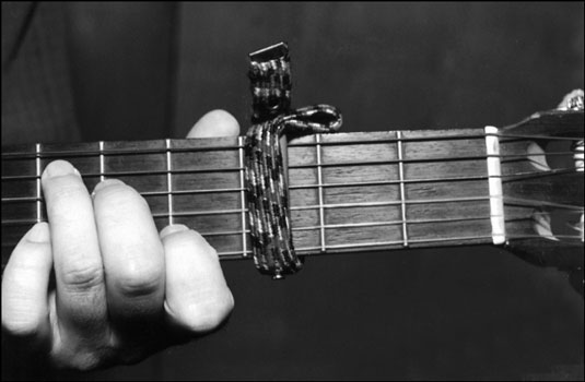A capo on the guitar neck. Notice that the capo sits just before the fret — not directly on t
