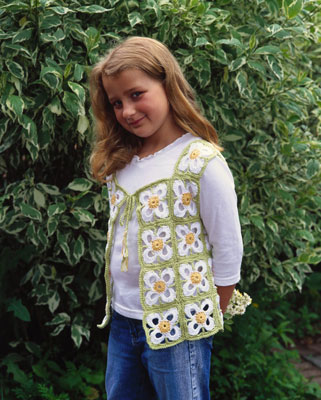 A young girl wears a crochet vest with a floral motif.