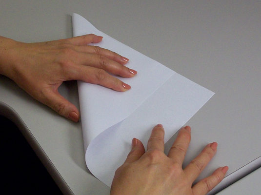 Folding two edges of a paper together.