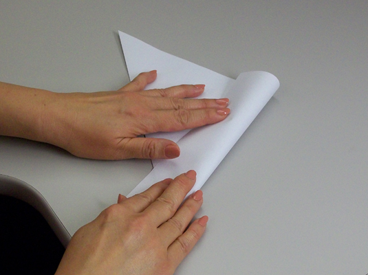 Folding the extra flap of paper over the edge next to it.