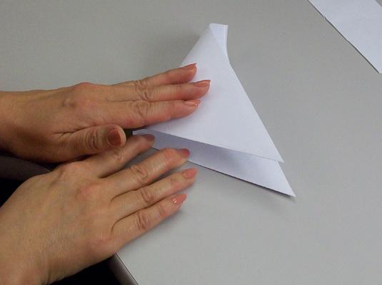 Folding a folded paper into a triangle.