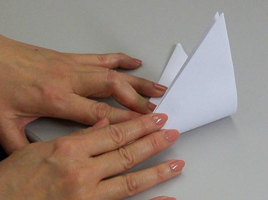 Folding a triangle into a smaller figure.