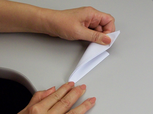 Folding a square paper into an eight-size triangle.