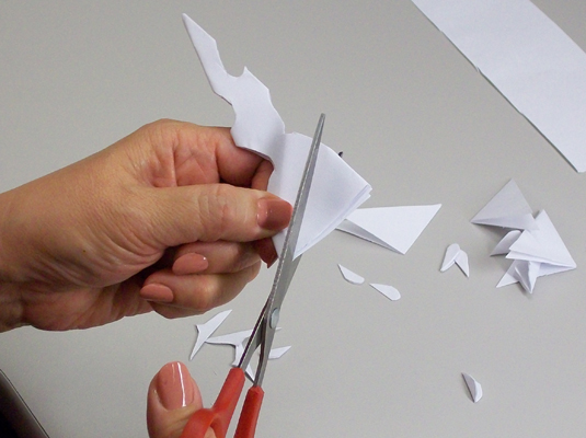 Cutting shapes out of a folded paper to make a snowflake.