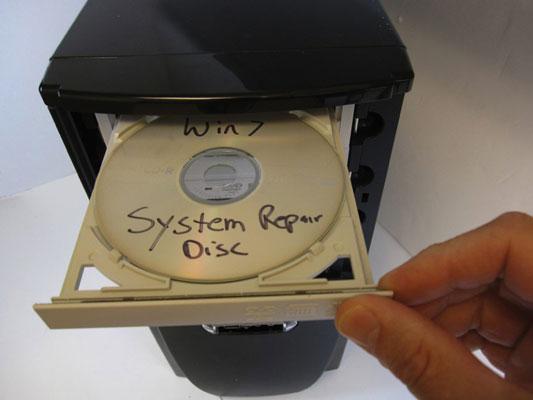 inserting a disc into a desktop's CPU.