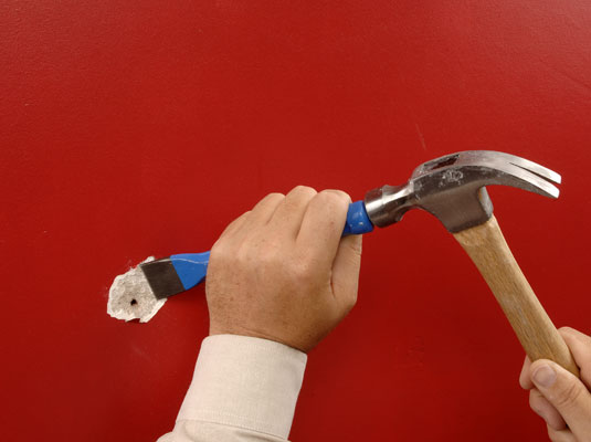 Hit the chisel with a hammer to widen the crack in the plaster.