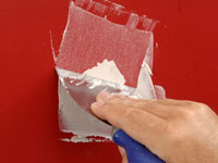 Use a putty knife to apply the plaster over the crack.