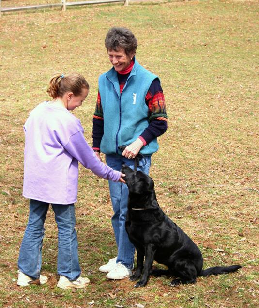 Girl pets a sitting black labrador.