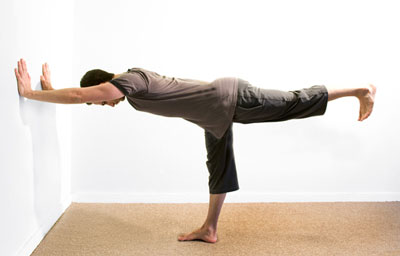 Man performs the Warrior at the wall posture