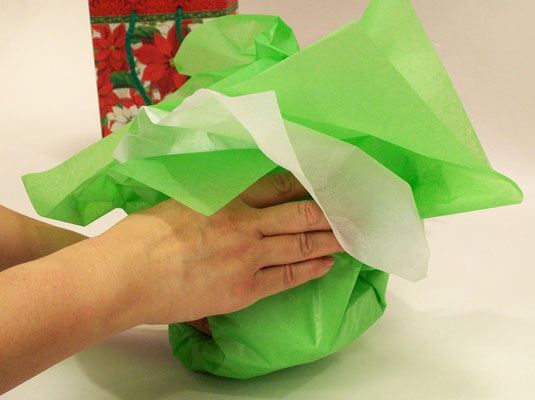 Gather up the tissue paper, loosely, over the gift.