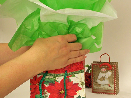 Placing the gift in a gift bag.