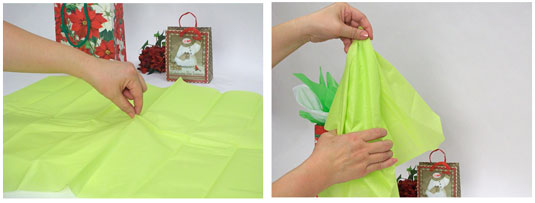 Adding more tissue paper to a gift bag.