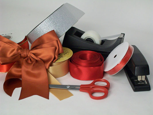Materials needed to make a bow from ribbon: ribbon, scissors, stapler, and tape.