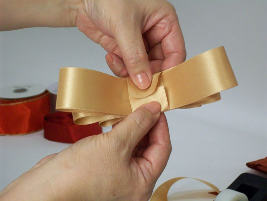 Finishing a bow with a piece of ribbon.