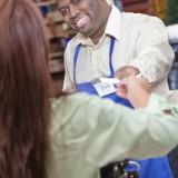 A cashier handing a receipt to a customer.