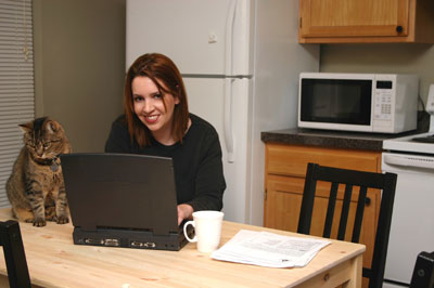 Woman sitting at a table with her laptop and cat.