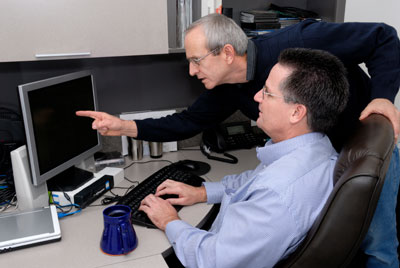 Two men discuss a project and make changes to it on the computer.