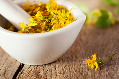 A mortar and pestle filled with flowers of St John's Wort.