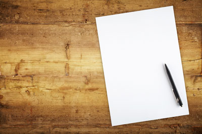 A pen and blank page on a wooden table.