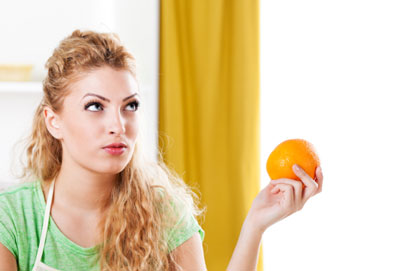 A young woman holding an orange.