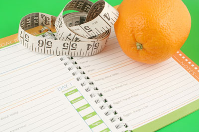 A planner, measuring tape and an orange.