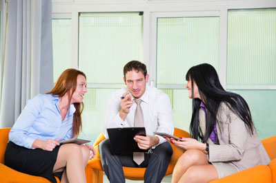 Three people in an office setting talking