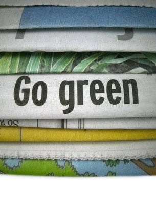 A stack of newspapers with the message Go Green.