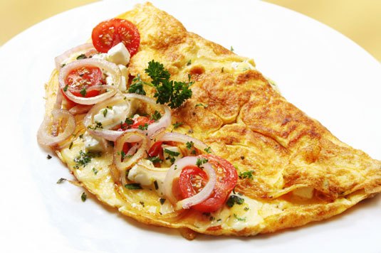 A cheese omelette with tomatoes and onions.