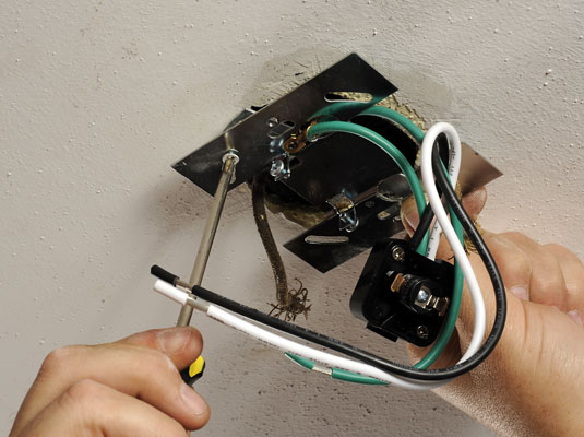 Attaching a mounting plate to the ceiling box.