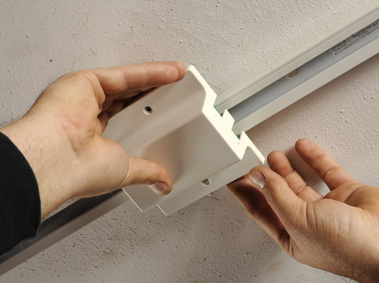Man installs the cover plate on the end of the track light.
