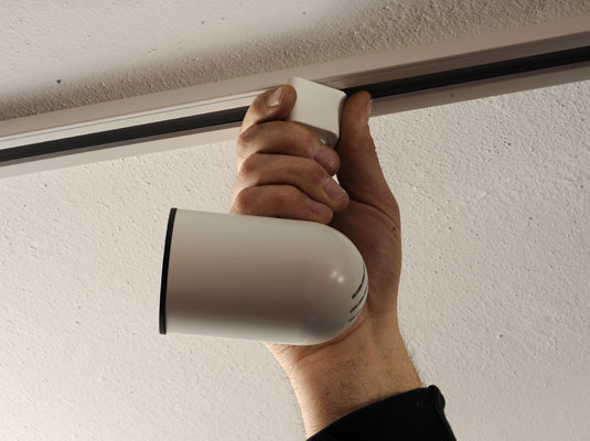 Mounting a light fixture on the ceiling.