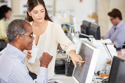 Two employees discussing a document open on a computer.