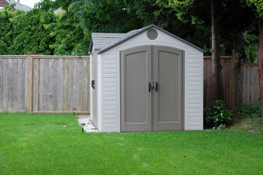 A garden shed in the far corner of a backyard.