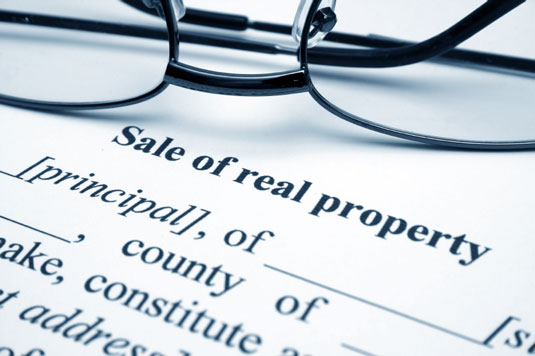 A pair of glasses over a real estate sale contract.