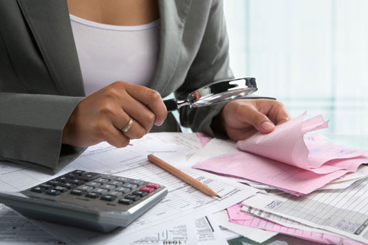 Woman goes over financial documents with a magnifying glass.
