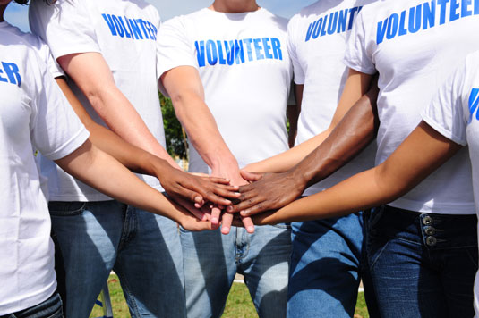 Group of volunteer with their hand put together.