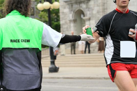 Volunteer in a race hands a drink to a runner.