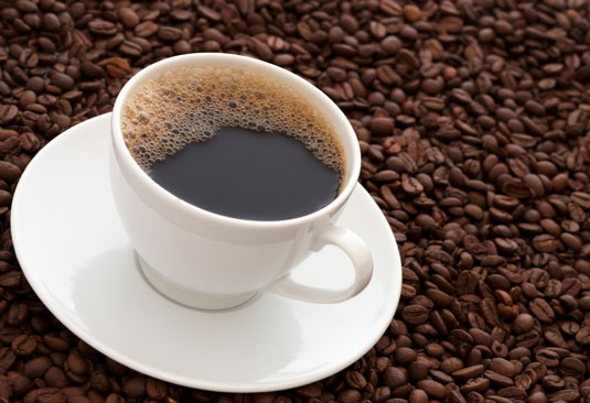 A cup of coffee surrounded by coffee grains.