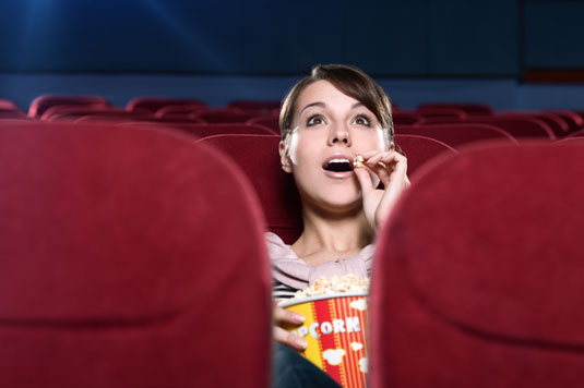 A woman watching a movie is surprised by something that happens in the movie.