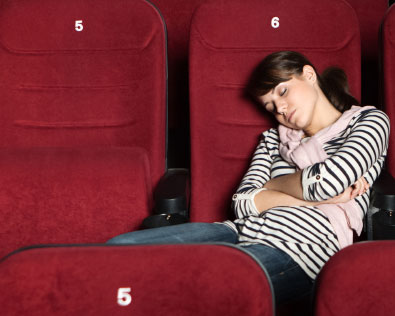 A woman sleeping in a movie theater.